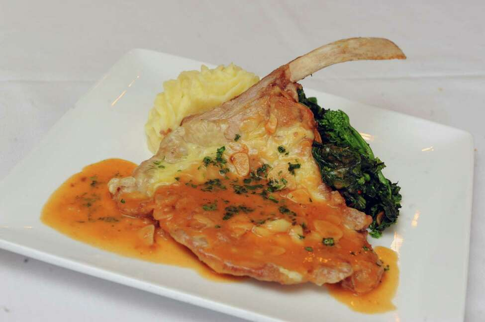 Veal chop topped with Fontina cheese served with garlic mash, broccoli and lemon jus at Rocco's restaurant on Wednesday June 10 2015 in Jonesville, N.Y. (Michael P. Farrell/Times Union)