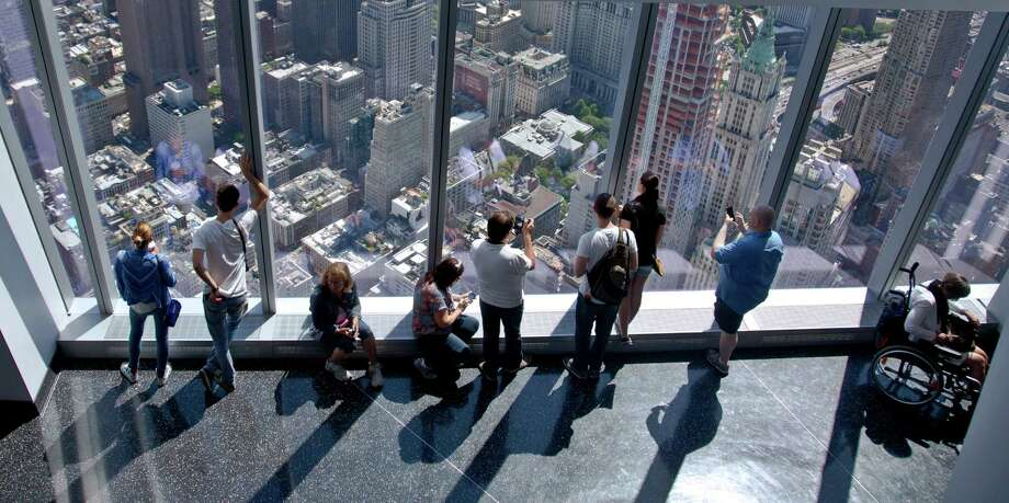 FILE - In this May 29, 2015 file photo, visitors to the One World Observatory view the city and beyond from the 101st floor in New York.  The World Trade Center observatory gives visitors a view of the city and its surroundings from above 1,250 feet, with sight lines stretching 50 miles past the Manhattan skyline. (AP Photo/Bebeto Matthews, File) ORG XMIT: NYET339 Photo: Bebeto Matthews / AP