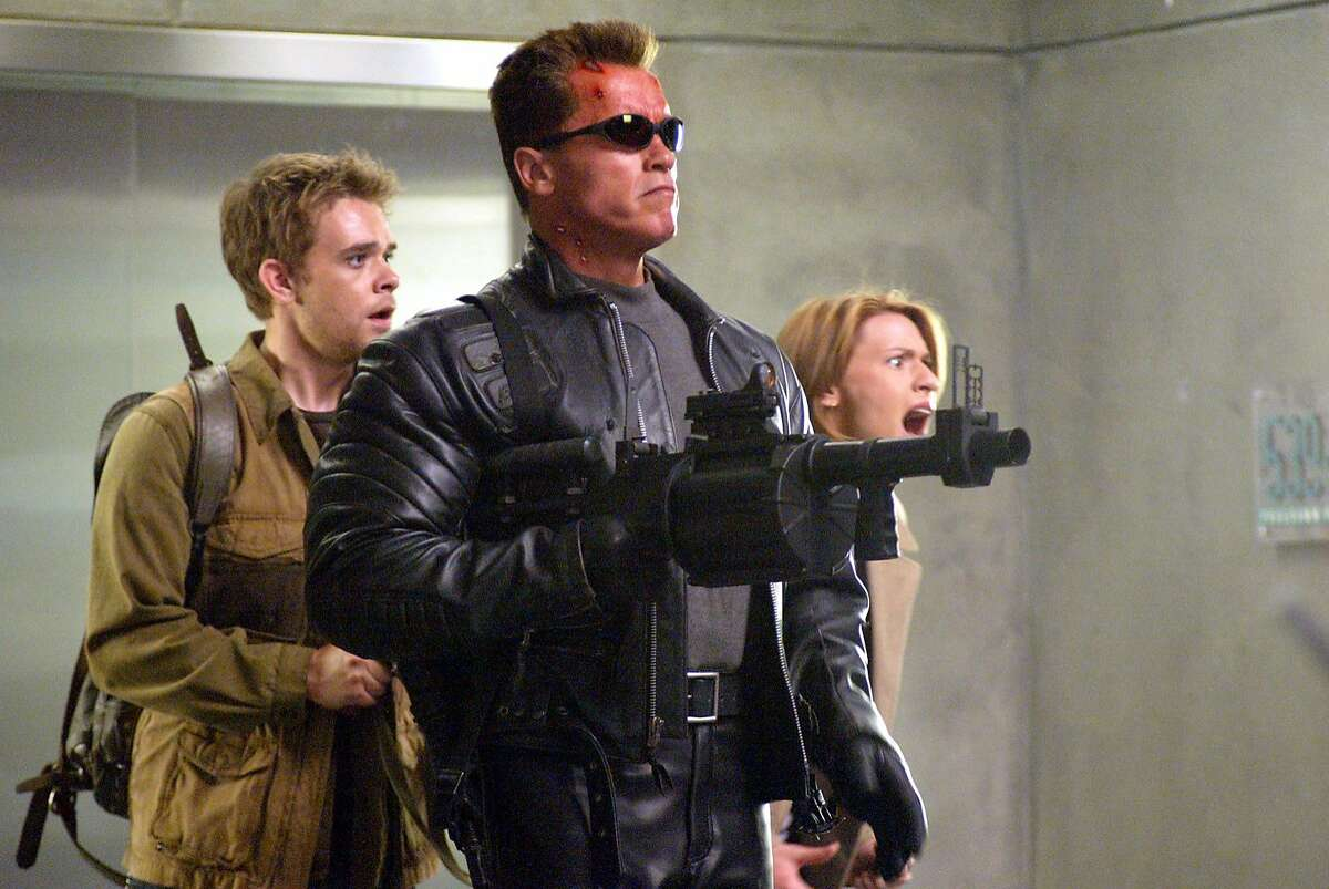 """TERMINATOR3 (L-r) NICK STAHL, ARNOLD SCHWARZENEGGER and CLAIRE DANES in the futuristic action thriller """"Terminator 3: Rise of the Machines,"""" distributed by Warner Bros. Pictures. PHOTOGRAPHS TO BE USED SOLELY FOR ADVERTISING, PROMOTION, PUBLICITY OR REVIEWS OF THIS SPECIFIC MOTION PICTURE AND TO REMAIN THE PROPERTY OF THE STUDIO. NOT FOR SALE OR REDISTRIBUTION A familiar face: Arnold Schwarzenegger, armed and decked out in leather, with Nick Stahl and Claire Daines in Terminator 3."""