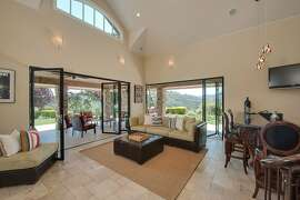 The spacious family room opens to a tile patio through two sets of accordion-style doors.