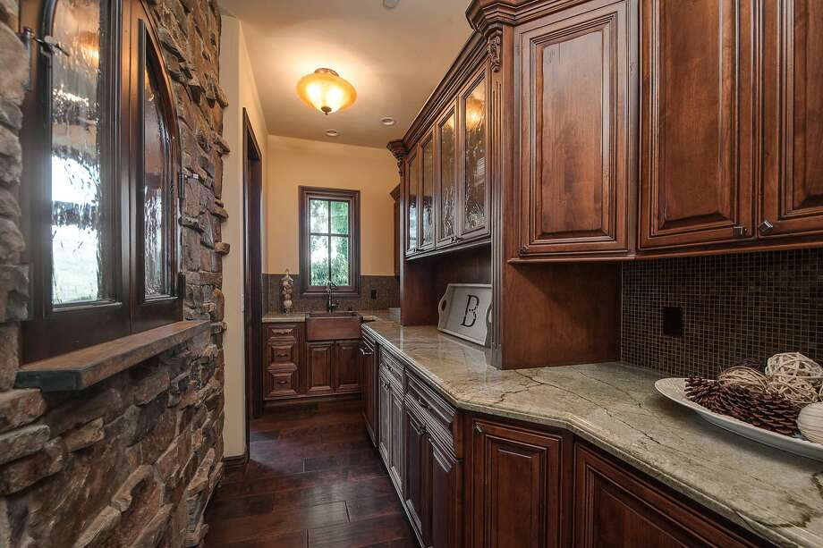 The kitchen features hand-carved cabinetry, a tile backsplash and a copper farmhouse sink.