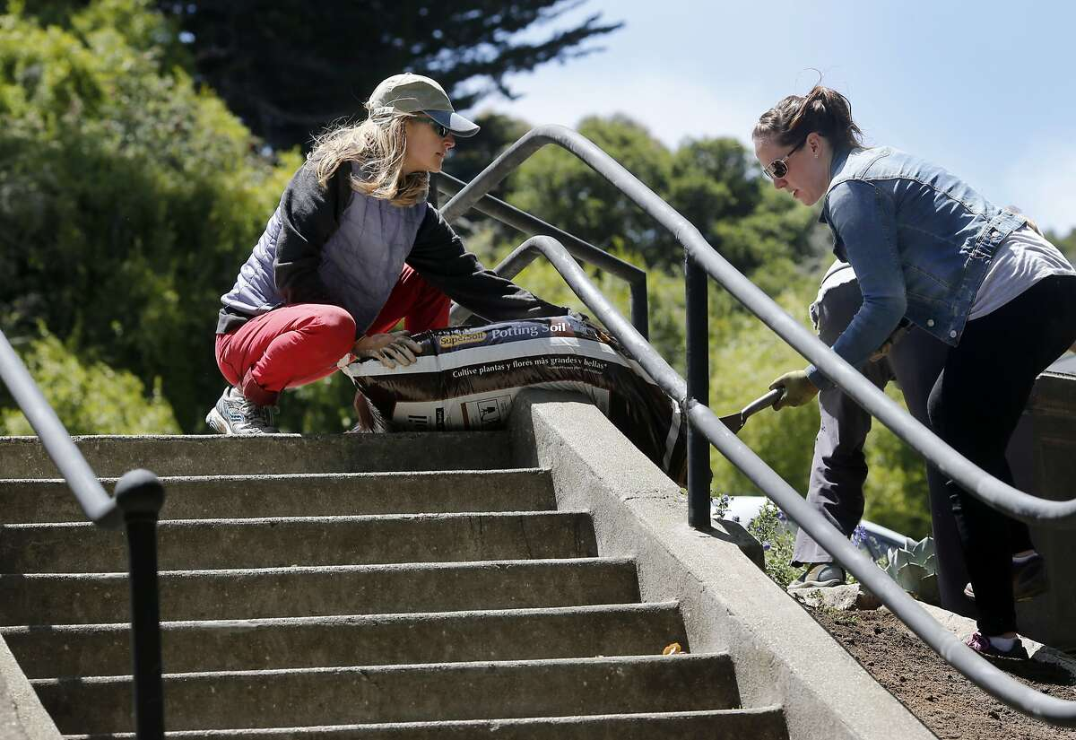 Amber Hasselbring (left) and Lindsay Faye worked together on a flower bed Thursday June 18, 2015. A stairway honoring urban explorer Adah Bakalinski near the east side of Buena Vista Park in San Francisco, Calif. will feature picturesque views, a new balustrade and colorful vegetation.