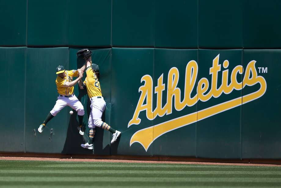 Billy Burns (left) and Josh Reddick fail to catch Melvin Upton Jr.'s eighth-inning drive for a triple. A subsequent collision left Reddick down. Photo: Jason O. Watson, Getty Images