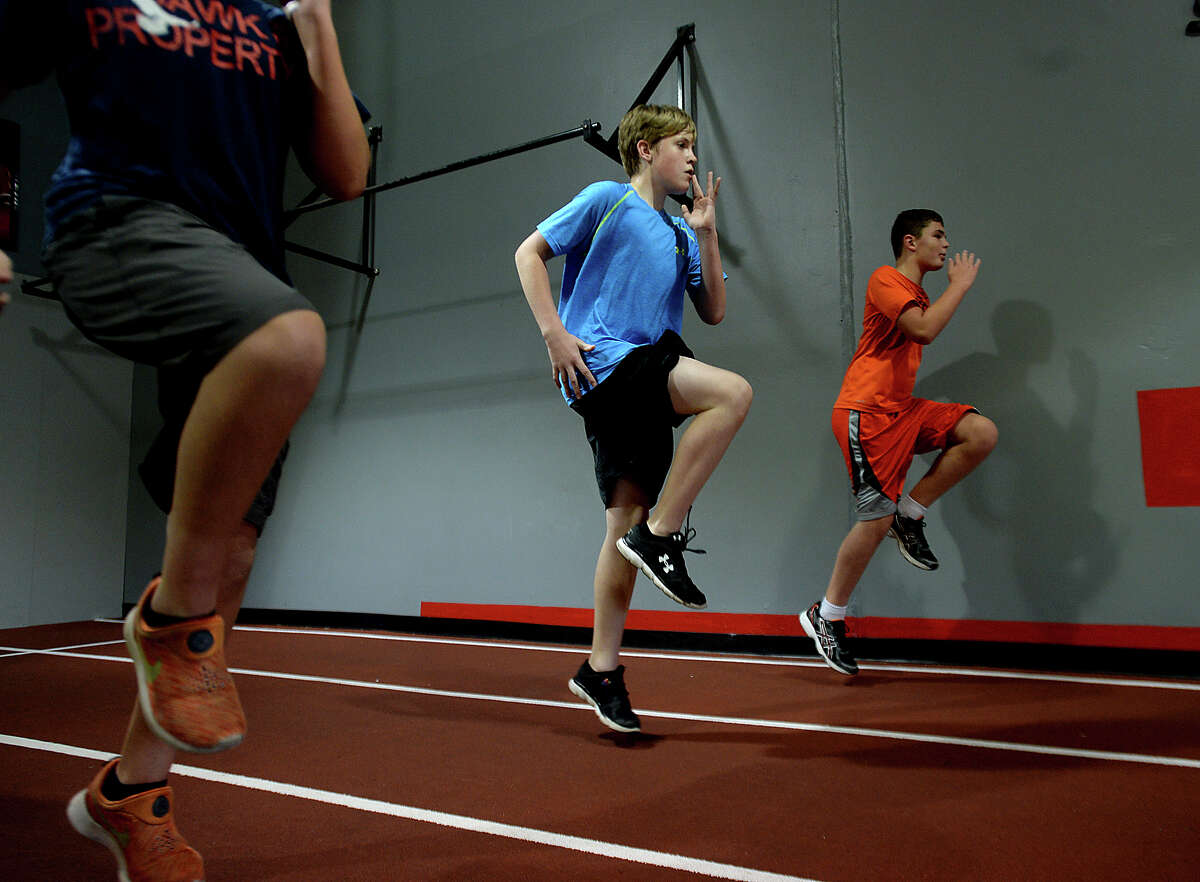 Cody Caldwell, 12, (left) and Griffin McClelland, 10, high step their way down the track during strength training at the Parisi Speed school of Beaumont. Instructor Brittney O'Pry is helping young athletes of all ages and abilities the opportunity to increase their ability through a combination of strength and speed training sessions. Photo taken Thursday, June 18, 2015 Kim Brent/The Enterprise