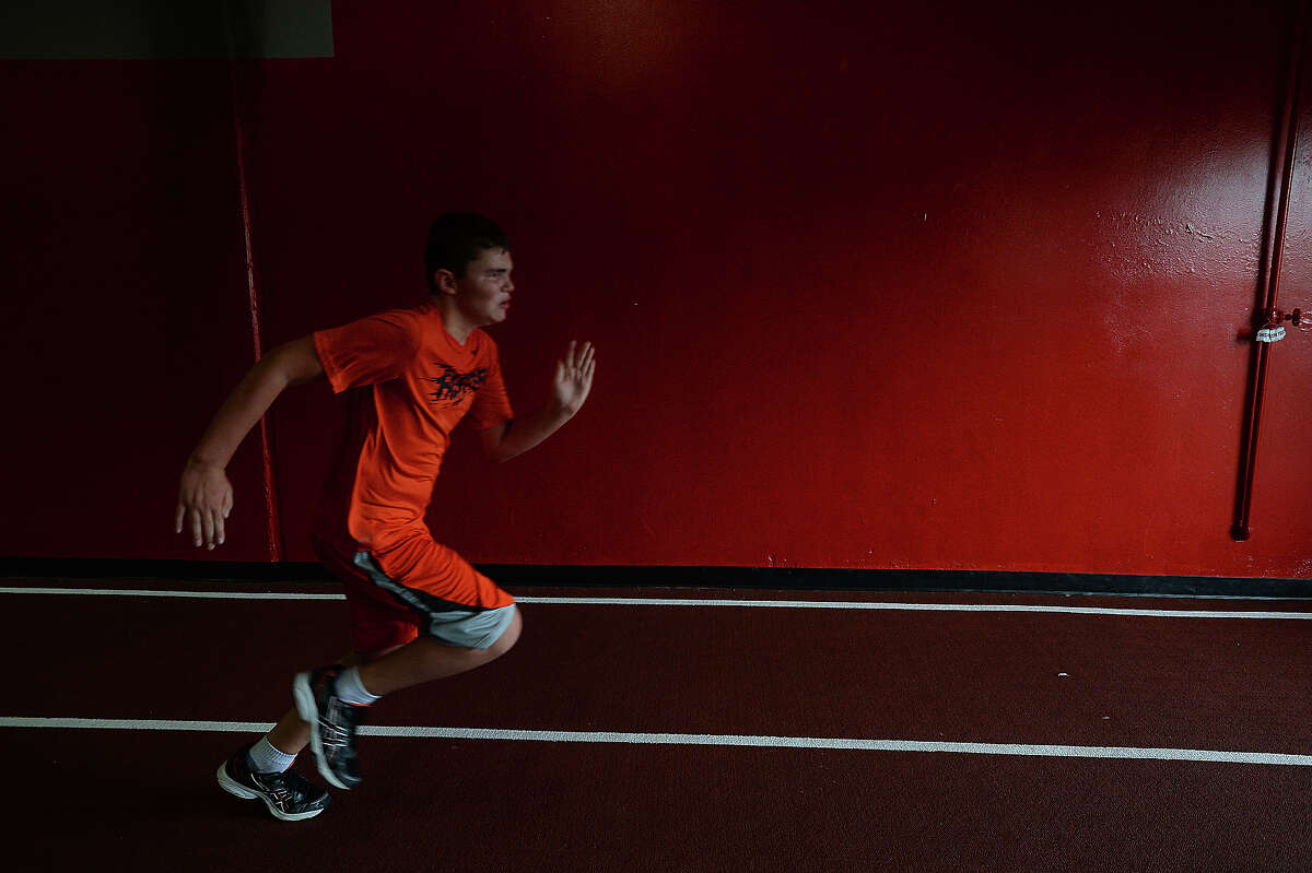 Griffin McClelland, 10, sprints down the track during strength training at the Parisi Speed school of Beaumont. Instructor Brittney O'Pry is helping young athletes of all ages and abilities the opportunity to increase their ability through a combination of strength and speed training sessions. Photo taken Thursday, June 18, 2015 Kim Brent/The Enterprise