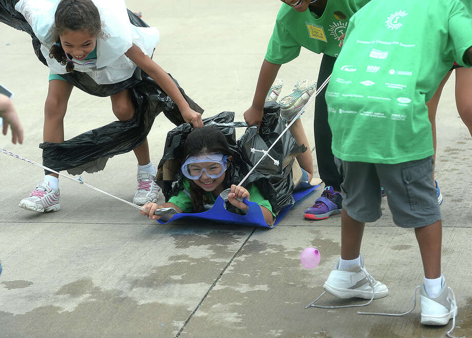 Team members laugh as they pull rider Hannah Anderson on their sled invention through an obstacle course on the final day of Invention Camp, which ran throughout the week at Regina Howell Elementary School. Seventy area school children participated in the program, which is in its sixth year. Using recycled materials, they worked on several different inventions, utilizing math, science and engineering skills.