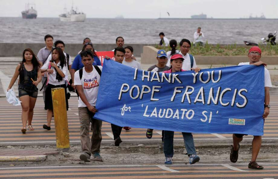 Environmental activists show their support for Pope Francis' encyclical on climate change with a banner as they march toward a Roman Catholic church in Manila, Philippines, on Thursday. Photo: Bullit Marquez, STF / AP