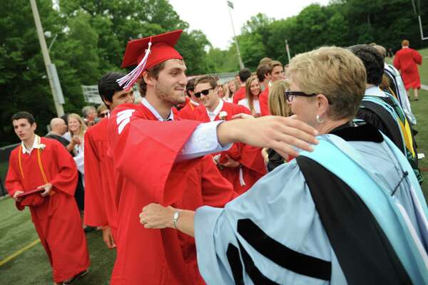 Justin Podlesak hugs Principal Dr. Veronica DeLuc following the 2015 New Canaan graduation ceremony at New Canaan High School's Dunning Stadium in New Canaan, Conn. Thursday, June 18, 2015.