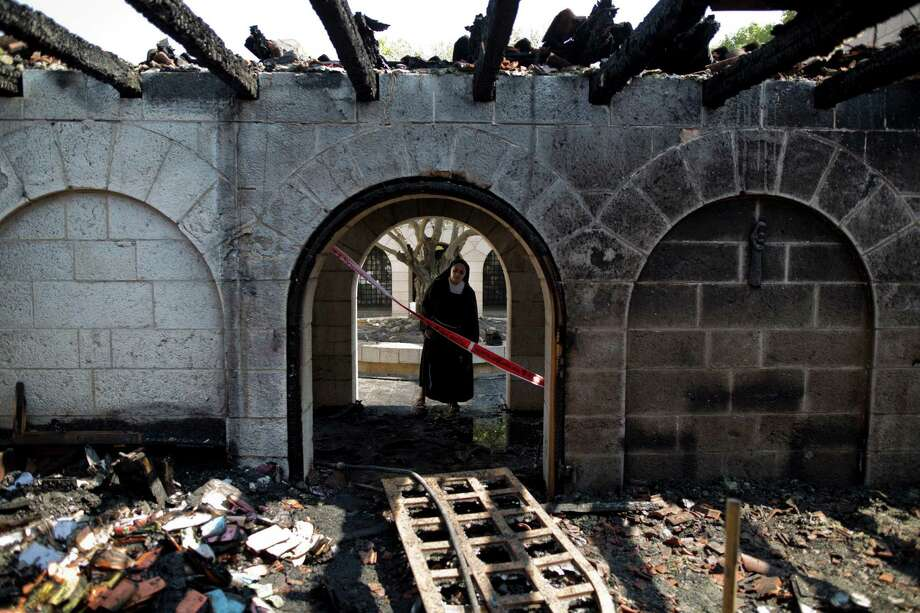 A nun surveys heavy damage at the Church of the Multiplication on Thursday after a fire broke out in the middle of the night near the Sea of Galilee in Tabgha, Israel. Police are investigating whether the fire was deliberate.  Photo: Ariel Schalit, STF / AP