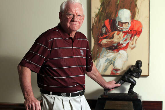 In 2013, John David Crow poses with the Heisman Trophy he won as a two-way player in 1957.