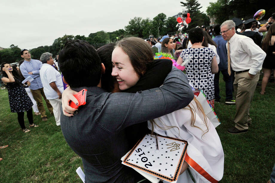 Iryna Zabolotna hugs her friends Danilo Oliva, left, and Laura Martinez, center, during the graduation ceremony at Stamford High School on Thursday. Photo: Jason Rearick / Hearst Connecticut Media / Stamford Advocate