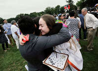 Iryna Zabolotna hugs her friends Danilo Oliva, left, and Laura Martinez, center, during the graduation ceremony at Stamford High School on Thursday.