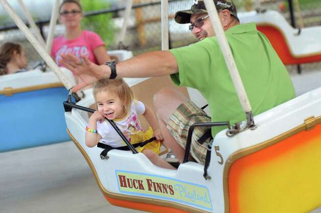 Riley May Beck, 2, center, of Albany delights in the hot air balloon ride with her father, Randy Beck, right, on Thursday, June 18, 2015, at Huck Finn's Playland in Albany, N.Y. The park's rides were acquired from the former Hoffman's Playland, which closed at the end of last summer. (Cindy Schultz / Times Union) Photo: Cindy Schultz / 00032316B