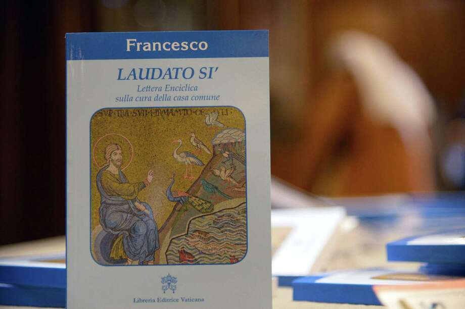 "A copy of Pope Francis's encyclical, a collection of principles to guide Catholic teaching, entitled ""Laudato Sii "" lies on a table during its official presentation, on June 18, 2015 at the Sinod hall at the Vatican. Pope Francis calls on the world's leaders to pull together to fight global warming, publishing his hotly-anticipated thesis on the environment which slams profiteers and slaves to progress. Released six months ahead of a key climate change meeting in Paris, Francis's text calls on international actors to take responsibility for ""new modes of production, distribution and consumption"", according to a leaked draft. AFP PHOTO / VINCENZO PINTOVINCENZO PINTO/AFP/Getty Images Photo: VINCENZO PINTO / AFP"