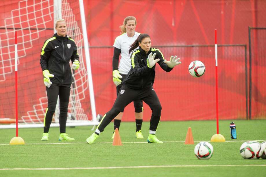 American goalkeeper Hope Solo (front) prepares to make a save as she and fellow keepers Ashlyn Harris (L) and Alyssa Naeher take part in a training session at the FIFA Women's World Cup in Edmonton, Canada on June 18, 2015.   AFP PHOTO/GEOFF ROBINSGEOFF ROBINS/AFP/Getty Images Photo: GEOFF ROBINS / AFP