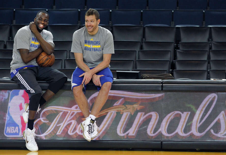 Draymond Green (left) took David Lee's starting position at the start of the season and then, in Game 3 of the NBA Finals, received a lesson from Lee about attacking on offense. They sat together as champions on the flight home after Game 6. Photo: Paul Chinn / Paul Chinn / The Chronicle / ONLINE_YES