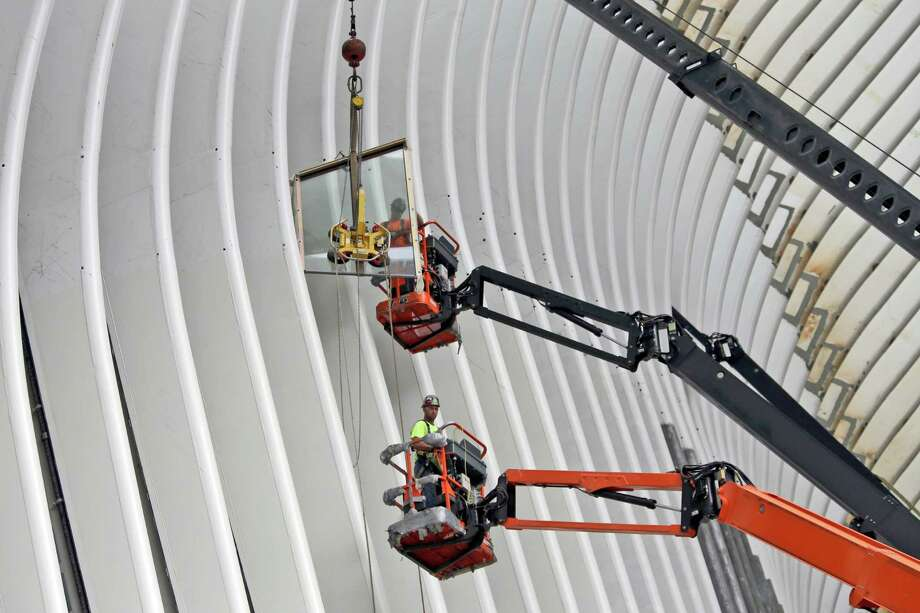 Construction workers install a glass panel on the Oculus structure at the World Trade Center transportation hub, Thursday, June 18, 2015, in New York. When the $3.9 billion transportation hub opens later this year, commuters and visitors will get to decide for themselves whether Spanish architect Santiago Calatrava's bird-in-flight design has been translated into a grand public space that justifies years of delays and cost overruns. (AP Photo/Mary Altaffer) ORG XMIT: NYMA120 Photo: Mary Altaffer / AP