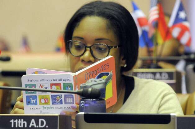 New York State Assembly member Kimberly Jean-Pierre, who is expected a child, looks over children's book between voting on bills during session at the Capitol on Thursday June 18, 2015 in Albany, N.Y.  (Michael P. Farrell/Times Union) Photo: Michael P. Farrell / 00032332A