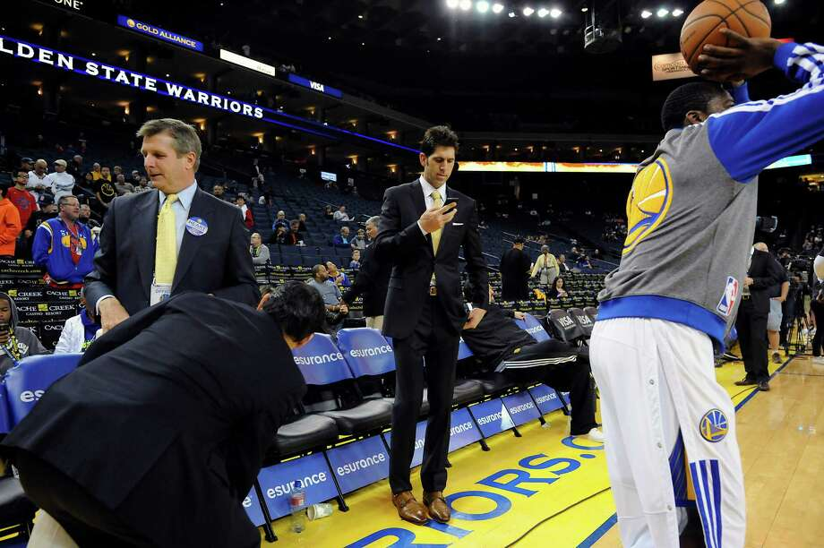 Golden State Warriors general manager Bob Myers checks his phone as players warm up before their game against the Brooklyn Nets at Oracle Arena in Oakland, CA Saturday, February 22, 2014. Photo: Michael Short / Special To The Chronicle / ONLINE_YES