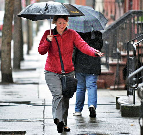 Elizabeth Gallagher of Albany doesn't seem to let the rain get her down as she makes her way back to work in Troy Tuesday March 12, 2013.  (John Carl D'Annibale / Times Union archive) Photo: John Carl D'Annibale