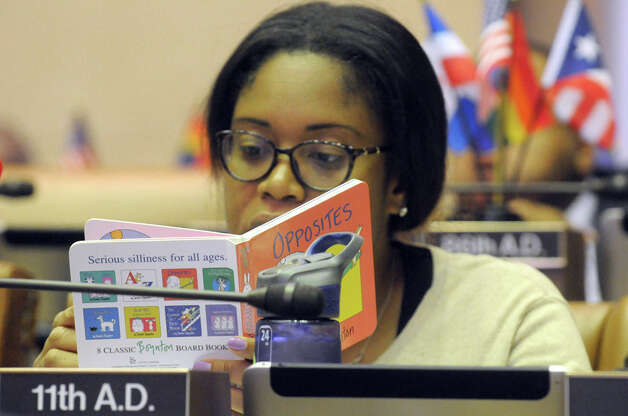 New York State Assembly member Kimberly Jean-Pierre, who is expected a child, looks over children's book between voting on bills during session at the Capitol on Thursday June 18, 2015 in Albany, N.Y.  (Michael P. Farrell/Times Union) Photo: Michael P. Farrell, Albany Times Union / 00032332A