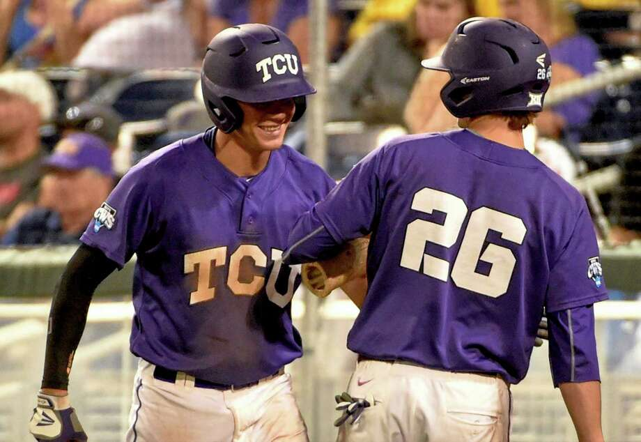Connor Wanhanen (left) celebrates with Keaton Jones after scoring in the seventh inning of the Horned Frogs' win. They now must beat Vanderbilt twice. Photo: Mike Theiler / Associated Press / FR170180 AP