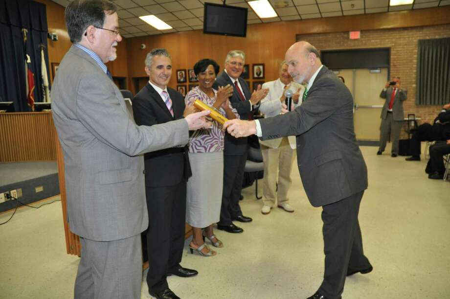 Interim Beaumont ISD Superintendent Vern Butler, right, hands a baton to the school district's new superintendent, John W. Frossard at a board meeting on June 18. Butler has served as interim superintendent for a year under the appointed Board of Managers, which took office, also a year ago. To Frossard's left are Lenny Caballero, Vernice Monroe, Jack Carroll and Jimmy Simmons.