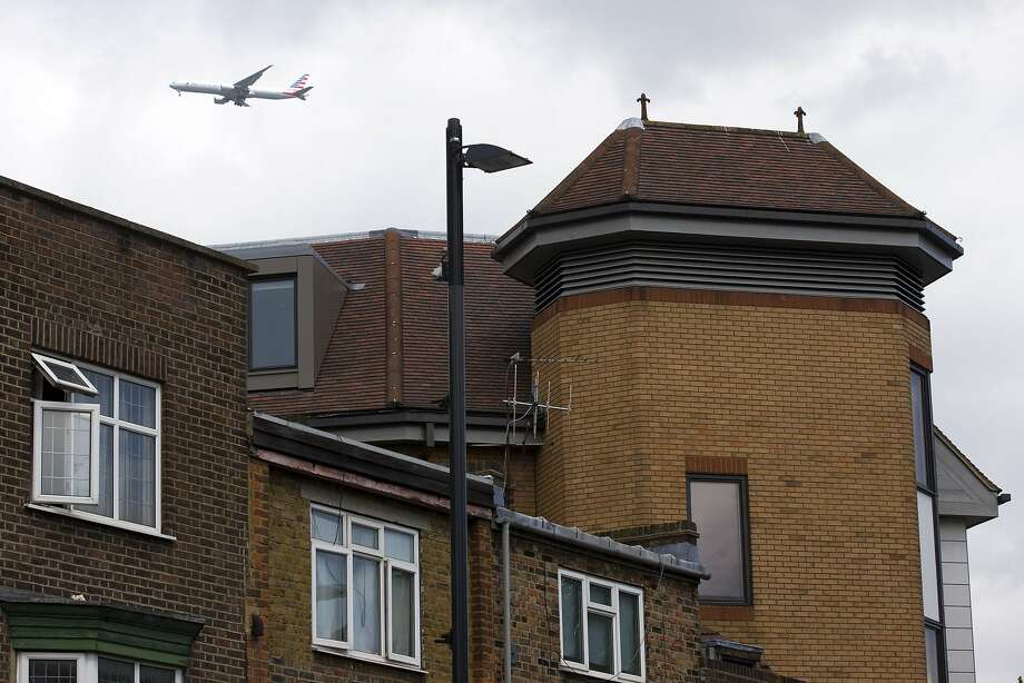 A plane flies past a suburb of London where the body of a dead man was found on an office roof. Photo: Justin Tallis, AFP / Getty Images