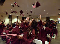 Savannah Adam, center, and other graduates toss their moartarboards into the air during the graduation ceremony for Trailblazers Academy in Stamford, Conn., on Friday, June 19, 2015.