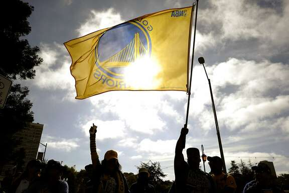 Fans wave a flag along Lake Merritt before the start of the Golden State Warriors Championship Parade in Oakland, CA Friday, June 19, 2015.
