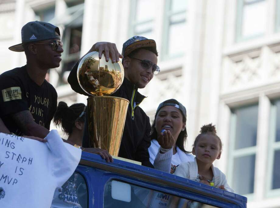 Stephen Curry holds the trophy while taking part in the Golden State Warriors NBA parade in Oakland. Photo: Wright, Douglas Zimmerman / SF Gate