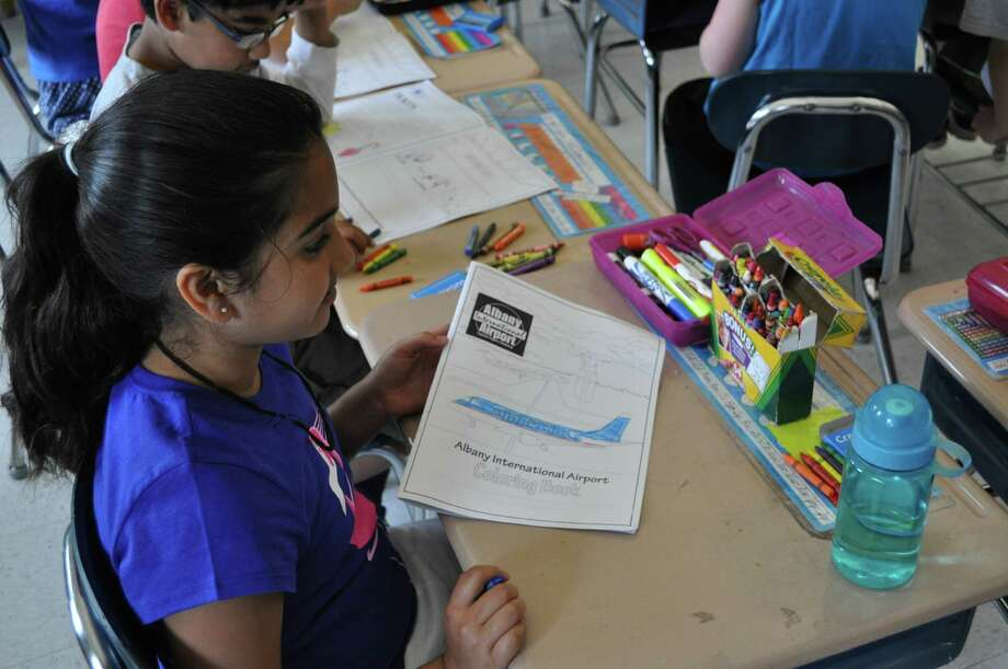 Riya Patel, a third-grade student at Blue Creek Elementary School in Latham, colors in a book created by Shaker High School students for the Albany International Airport on Friday, June 19, 2015. (Photos provided by Albany International Airport)