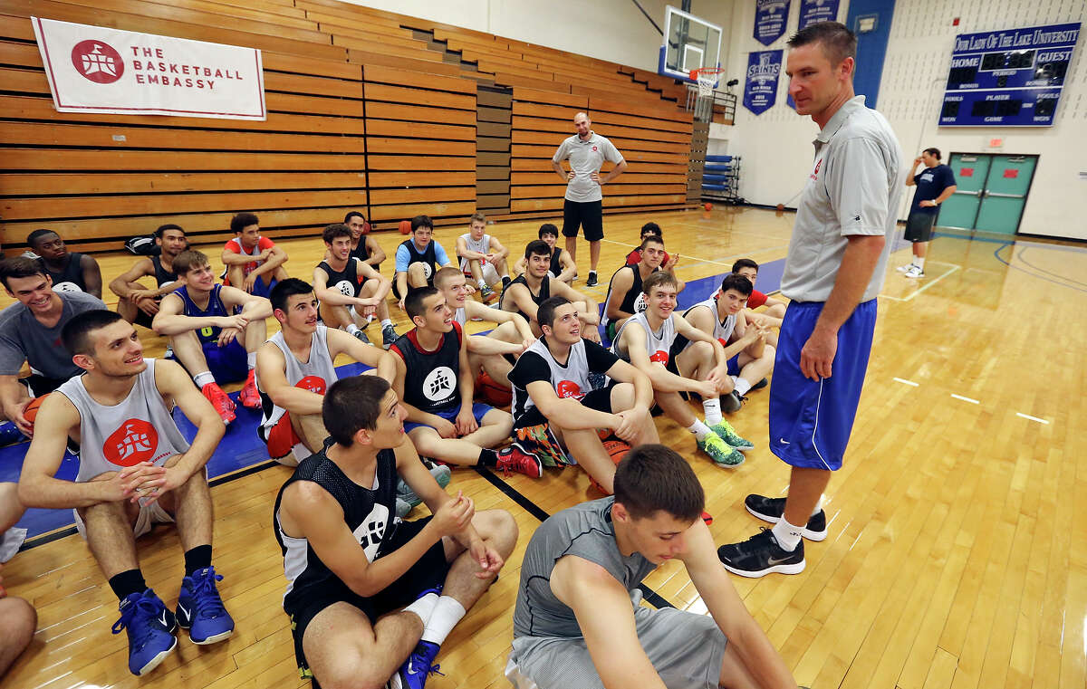 Chris Dial, executive director of The Basketball Embassy, (right) talks with players during The Basketball Embassy's inaugural Assembly 2015 camp Thursday June 18, 2015 at Our Lady of the Lake University's Mabee Gym.
