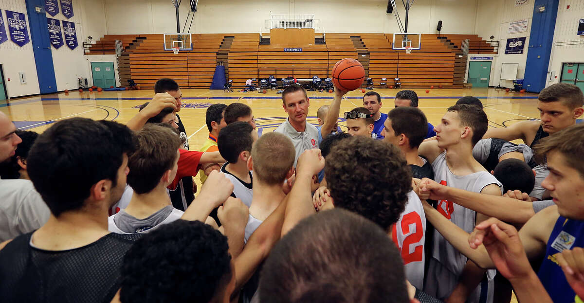 Chris Dial, executive director of The Basketball Embassy, (center) huddles with players and coaches during The Basketball Embassy's inaugural Assembly 2015 camp Thursday June 18, 2015 at Our Lady of the Lake University's Mabee Gym.