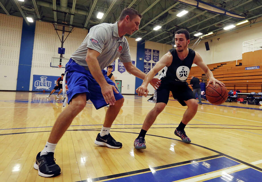 Chris Dial, executive director of The Basketball Embassy, (left) works with Deniz Simnica, 15 from Prishtina, Kosovo,   during The Basketball Embassy's inaugural Assembly 2015 camp Thursday June 18, 2015 at Our Lady of the Lake University's Mabee Gym. Photo: Edward A. Ornelas, Staff / San Antonio Express-News / © 2015 San Antonio Express-News