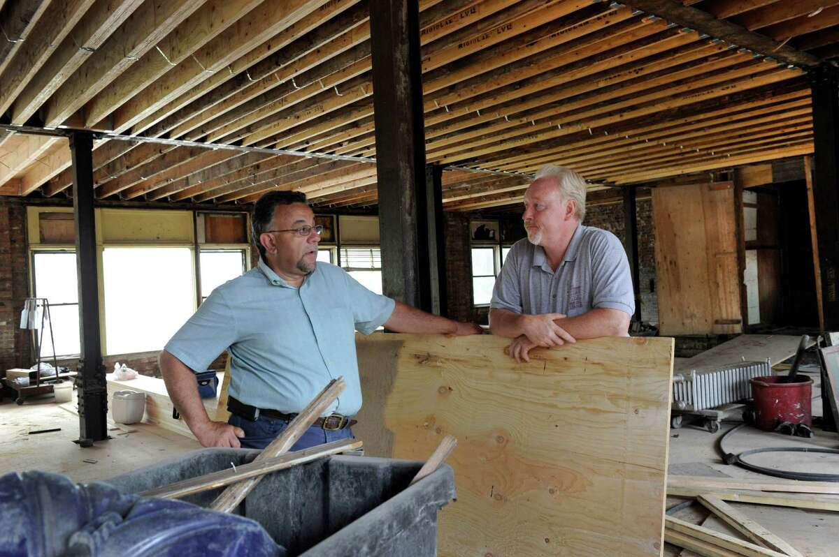 """Joe DaSilva, left, chats with Jeff Fish, building superintendent at the Pershing Building Wednesday, June 17. The Pershing Building at the corner of Main and West Streets in Danbury is being fitted for a """"future tenant"""" Wednesday, June 17, 2015. Joe DaSilva, the building's owner, can't say who it is but Naugatuck Valley Community College has already said that's where they intend to expand."""
