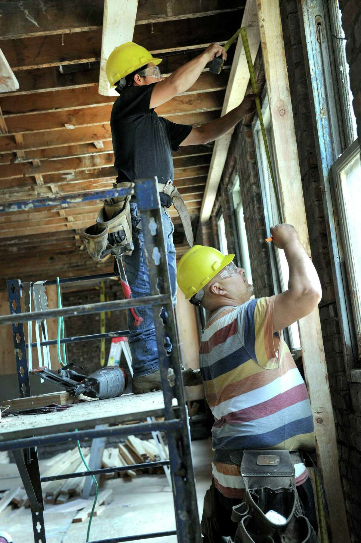 """Manuel Guzman, left, and Marcelo Moura work on the inside space of the Pershing Building Wednesday, June 17. The Pershing Building at the corner of Main and West Streets in Danbury is being fitted for a """"future tenant"""" Wednesday, June 17, 2015. Joe DaSilva, the building's owner, can't say who it is but Naugatuck Valley Community College has already said that's where they intend to expand."""