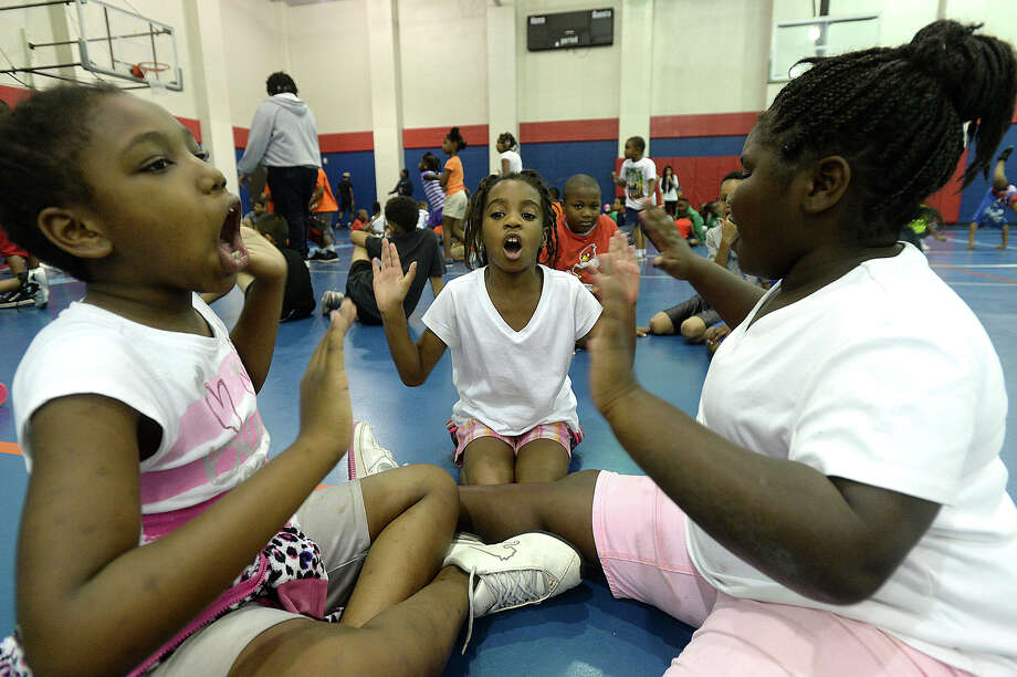 "From left, Ty'Neesia Thomas, Anayah Shankle, and Madison Ryals, all 8, play ""lemonade"" during free play Wednesday afternoon for children enrolled in the Learn and Grow at Day Camp program at the Sterling Pruitt Activity Center. More than 200 children are enrolled for the first session, which started this week and runs through July. The day-long camp is Monday through Friday, offering participants a number of activities, ranging from sports to arts and crafts and field-trips. A second session starts in mid-July and runs through August, with openings remaining for new enrollees.  Photo taken Wednesday, June 17, 2015 Kim Brent/The Enterprise Photo: Kim Brent / Beaumont Enterprise"