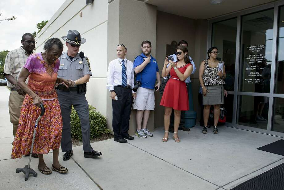 """People arrive for a bond hearing in Charleston, S.C. Dylann Roof faces nine counts of murder in a rampage that NAACP national President Cornell William Brooks condemned as """"an act of racial terrorism."""" Photo: Brendan Smialowski, AFP / Getty Images"""