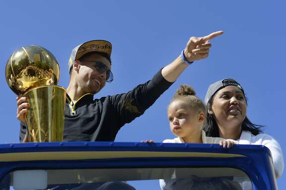 Stephan Curry, Ayesha Curry, and their daughter Riley Curry ride down Broadway Street for the parade celebrating the Golden State Warriors first NBA Final win in 40 years in Oakland, California, on Friday, June 19, 2015.