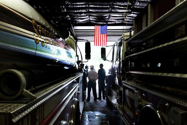 John Wolfe, chairman of the building committee, left and Mary Pierce, president of the fire company, stand under the American flag in the apparatus bay of the temporary fire house at the announcement of FEMA funds Friday morning June 19, 2015,  to build a new firehouse for the Schoharie Niagara Engine 6 Fire Company       (Skip Dickstein/Times Union) Photo: SKIP DICKSTEIN / 00032335A