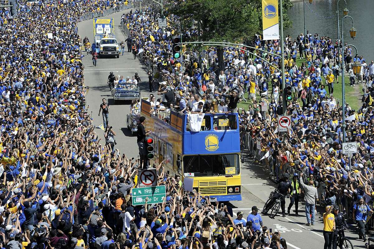 Stephen Curry waves to fans along Lake Merritt during the Golden State Warriors Championship Parade in Oakland, CA Friday, June 19, 2015.