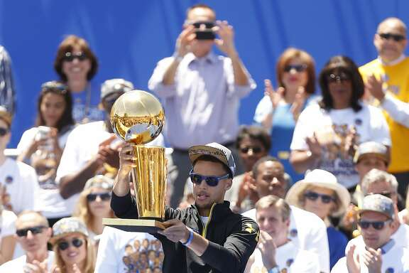Golden State Warriors' Stephen Curry hoists the trophy after being introduced during the NBA Champions rally at the Henry J. Kaiser Convention Center on Friday, June 19, 2015 in Oakland, Calif.
