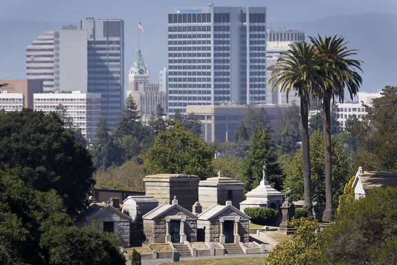 The downtown skyline rises behind mausoleums at Mountain View Cemetery in Oakland, Calif. on Friday, June 19, 2015. The resting place for over 177,000 souls celebrates its 150th anniversary on Saturday.
