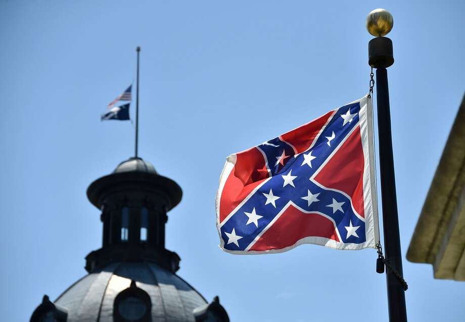 The South Carolina and US  flags are seen flying at half-staff behind the Confederate flag erected in front of the State Congress building in Columbia, South Carolina on June 19, 2015. Police captured the white suspect in a gun massacre at one of the oldest black churches in Charleston in the United States, the latest deadly assault to feed simmering racial tensions. Police detained 21-year-old Dylann Roof, shown wearing the flags of defunct white supremacist regimes in pictures taken from social media, after nine churchgoers were shot dead during bible study on Wednesday. AFP PHOTO/MLADEN ANTONOVMLADEN ANTONOV/AFP/Getty Images Photo: Mladen Antonov, AFP / Getty Images