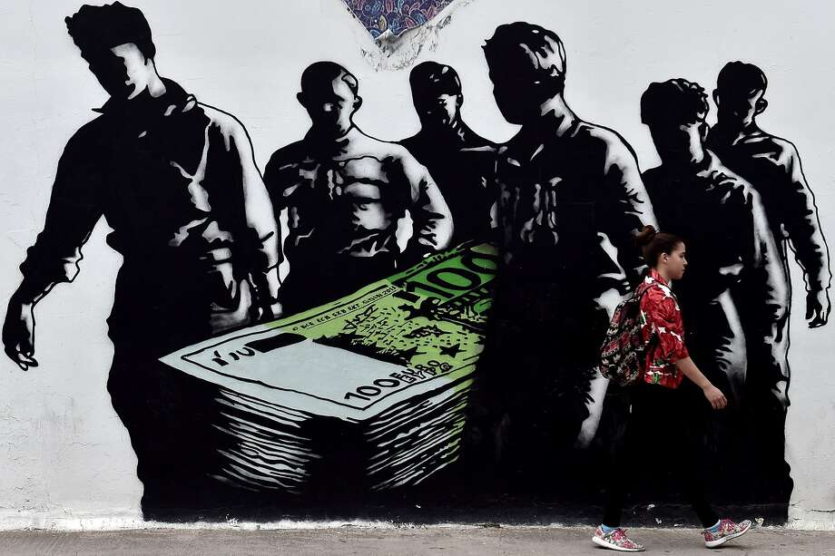 "A young woman walks past a graffiti called ""Death of Euro"" by French street artist Goin, in Athens. Photo: Aris Messinis, AFP / Getty Images"