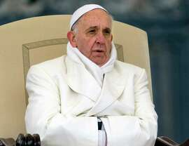 In this 2013 file photo Pope Francis tries to keep himself warm as he attends his weekly general audience in St. Peter's Square at the Vatican. Pope Francis released his much-anticipated encyclical 'Laudato Si' (Praise Be), on the environment Thursday, declaring an urgent need for the political and spiritual conversion of global leaders and individuals to dedicate themselves to curbing climate change and ending policies and personal habits that destroy creation.