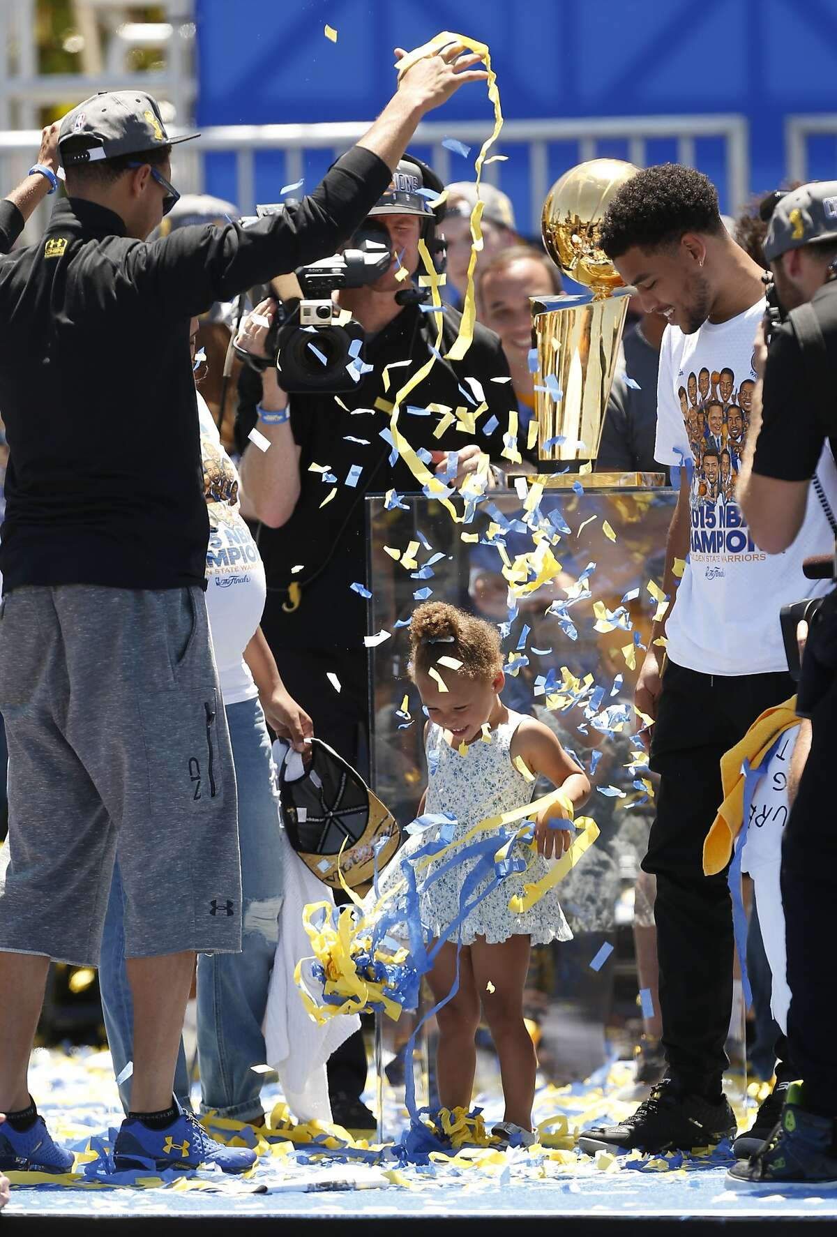 Golden State Warriors' Stephen Curry drops confetti on his daughter, Riley, during the NBA Champions rally at the Henry J. Kaiser Convention Center on Friday, June 19, 2015 in Oakland, Calif.