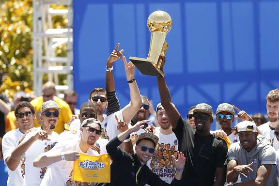 Golden State Warriors' Draymond Green hoists the trophy during the NBA Champions rally at the Henry J. Kaiser Convention Center on Friday, June 19, 2015 in Oakland, Calif.