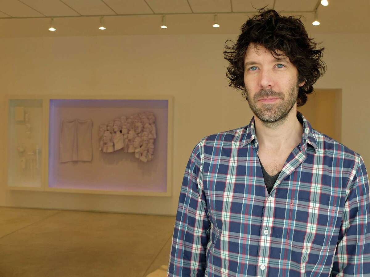 """Michael Jones McKean has his first solo show at Inman Gallery. """"A hundred twenty-six billion acres"""" is on view through July 11. Behind him is the diptych relief """"we are see-through we never die."""""""
